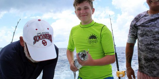 boy in green shirt holding a baracuda on a deep sea fishing trip in Cozumel